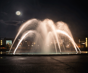 Night view of the water feature in the Penn State Arboretum. Lights reflect off the water as it sprays in formation.