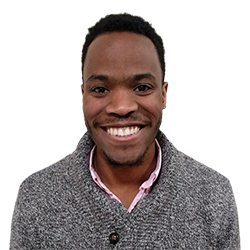 African-American male in his mid twenties with short dark brown hair. Wearing a gray sweater.