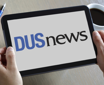 Man holding an electronic table with the words DUS News on the screen.