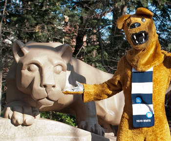 The Nittany Lion Mascot posing with the Nittany Lion Shrine.