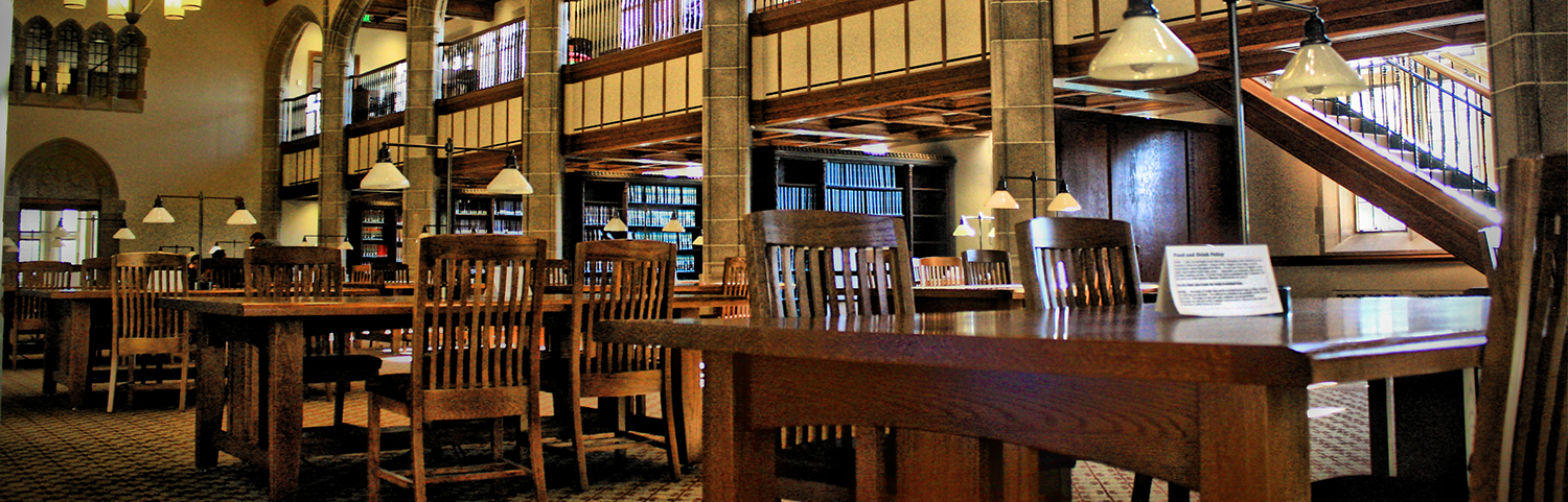 Library at a law school with brown wooden chairs and tables in front of rows of bookshelves.