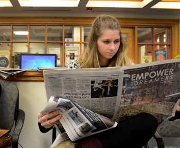 Student looking at newspaper.