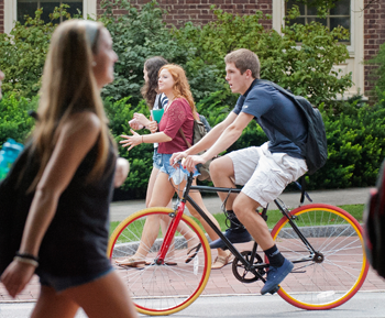Male student riding bike through the University Park campus.